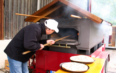 Albkorn-Bäcker Hans Wucherer schiebt Flammkuchen in den Holzbackofen