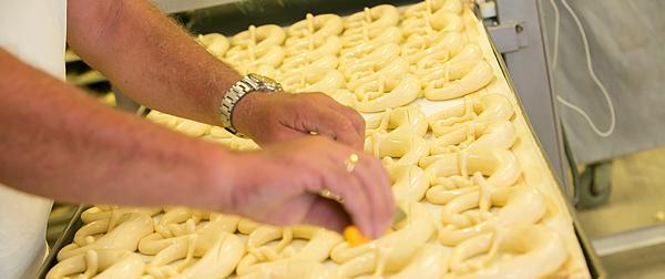 Bäckerhände schneiden Brezeln vor dem Backen ein