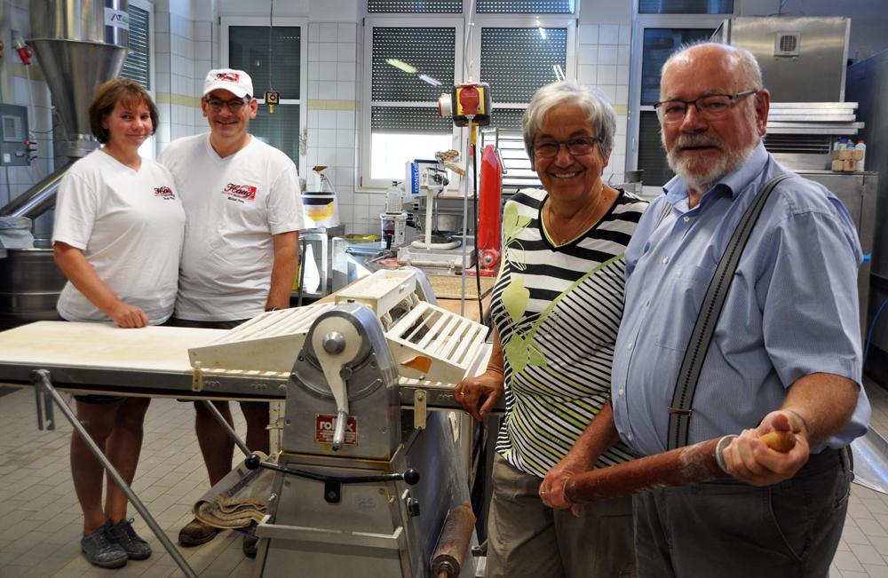 Bäckermeister Wolfgang Haug hält ein Nudelholz, daneben seine Frau Margarethe, hinter der Ausrollmaschine sein Sohn Michael mit Ehefrau Birgit Haug.
